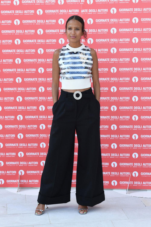 Nữ diễn viên kiêm đạo diễn người Pháp Mati Diop trong trang phục quần jean xanh ống loe, cạp cao của thương hiệu Miu Miu.