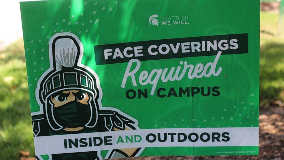 Áp phích bên ngoài tòa nhà Hội Sinh viên Đại học tiểu bang Michigan yêu cầu sinh viên MSU về việc đeo khẩu trang cả bên ngoài và bên trong khuôn viên trường - Ảnh: AP