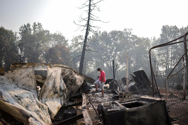 Một người đàn ông bên đống đổ nát do cháy rừng tàn phá ở Phoenix, Oregon