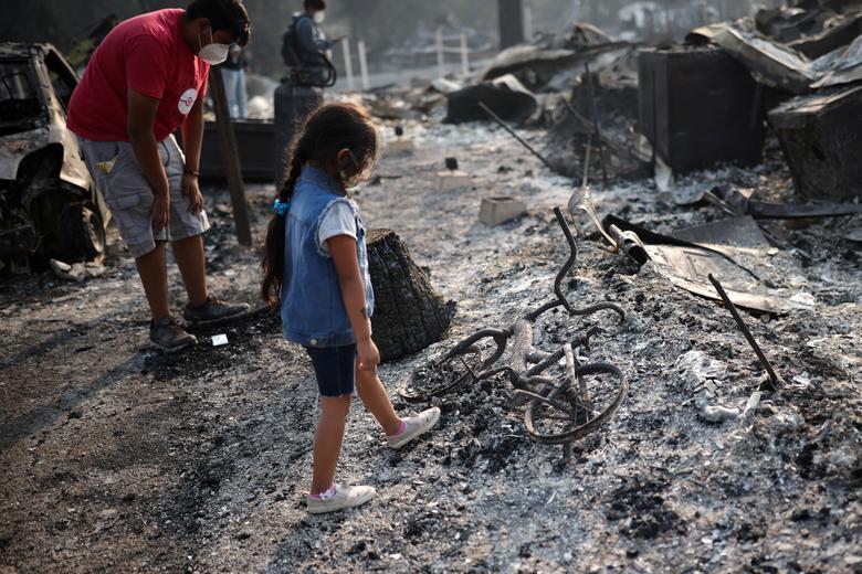 Cô bé Ashley bên cạnh chiếc xe đạp bị cháy của mình sau khi vụ cháy rừng thiêu rụi một khu phố ở  Bear Creek, Phoenix, Oregon