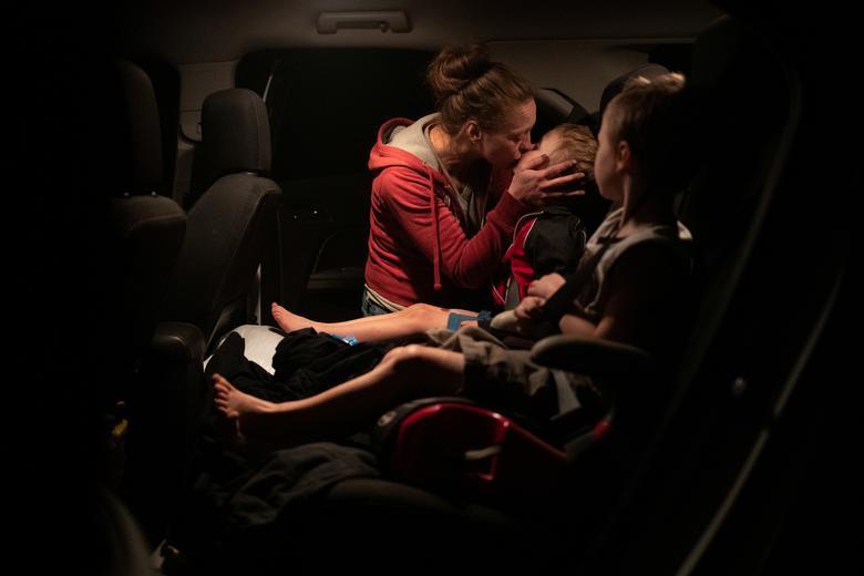 Một phụ nữ hôm hai cậu con trai sinh đôi 4 tuổi trước khi các bé được đưa đi sơ tán cùng gia đình chị dâu