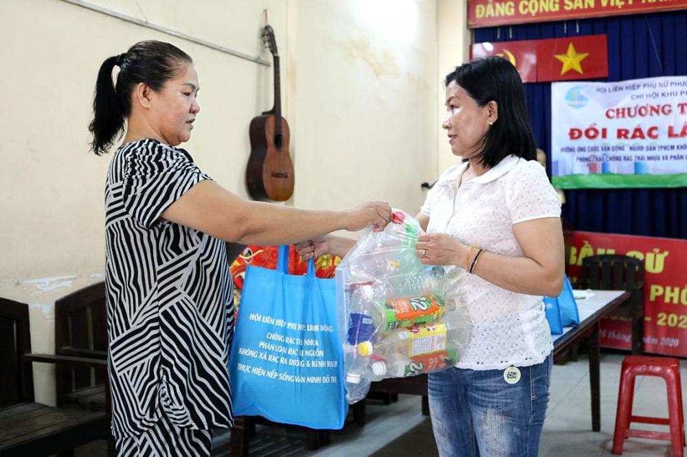 """Chi hội Phụ nữ khu phố thực hiện chương trình  """"Đổi rác lấy gạo"""", chị Thuy (bìa phải) chở thêm quà lên tặng bà con"""