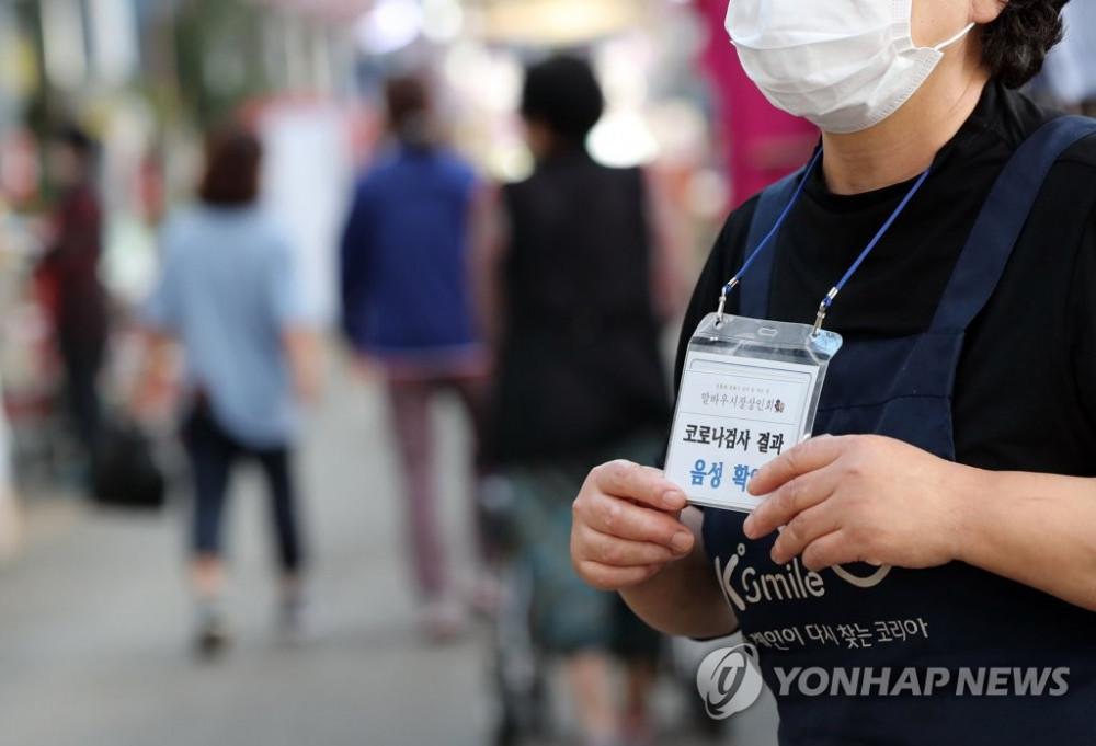 Một người bán hàng tại khu chợ truyền thống ở Gwangju, cách thủ đô Seoul 330 km về phía nam, đeo tấm biển thông báo cho khách hàng rằng cô ấy đã xét nghiệm âm tính với COVID-19.