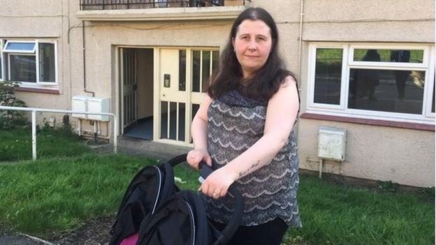 Người mẹ 3 con Abigail McManus cố gắng đưa chiếc xe đẩy 2 chỗ vào căn hộ của mình - Ảnh: BBC News