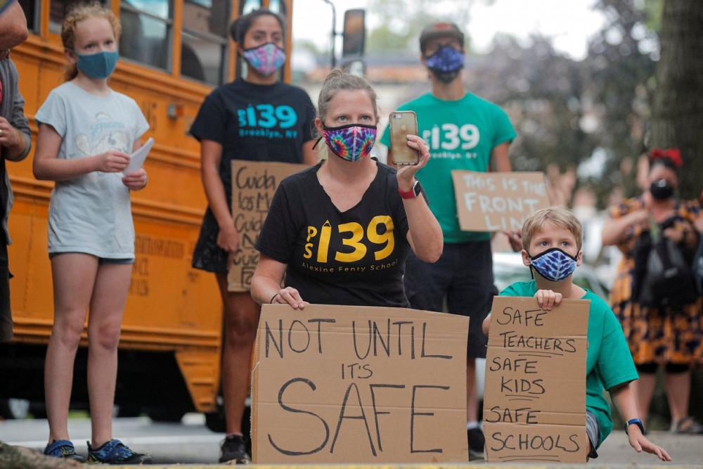 Phụ huynh và học sinh biểu tình hôm thứ Hai (14/9) nhằm phản đối việc cho phép trường học mở cửa trở lại khi ngành giáo dục chưa có sự chuẩn bị kỷ càng - Ảnh: Brendan McDermid/Reuters