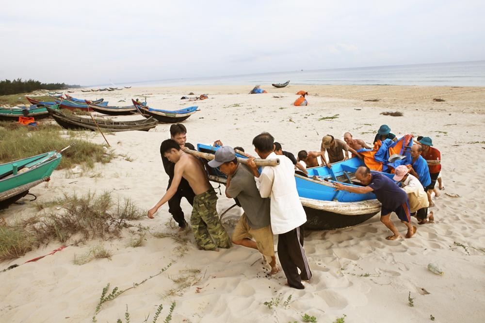 Ngư dân tỉnh Thừa Thiên - Huế đưa thuyền vào bờ để tránh bão số 5 - Ảnh: Thuận Hóa