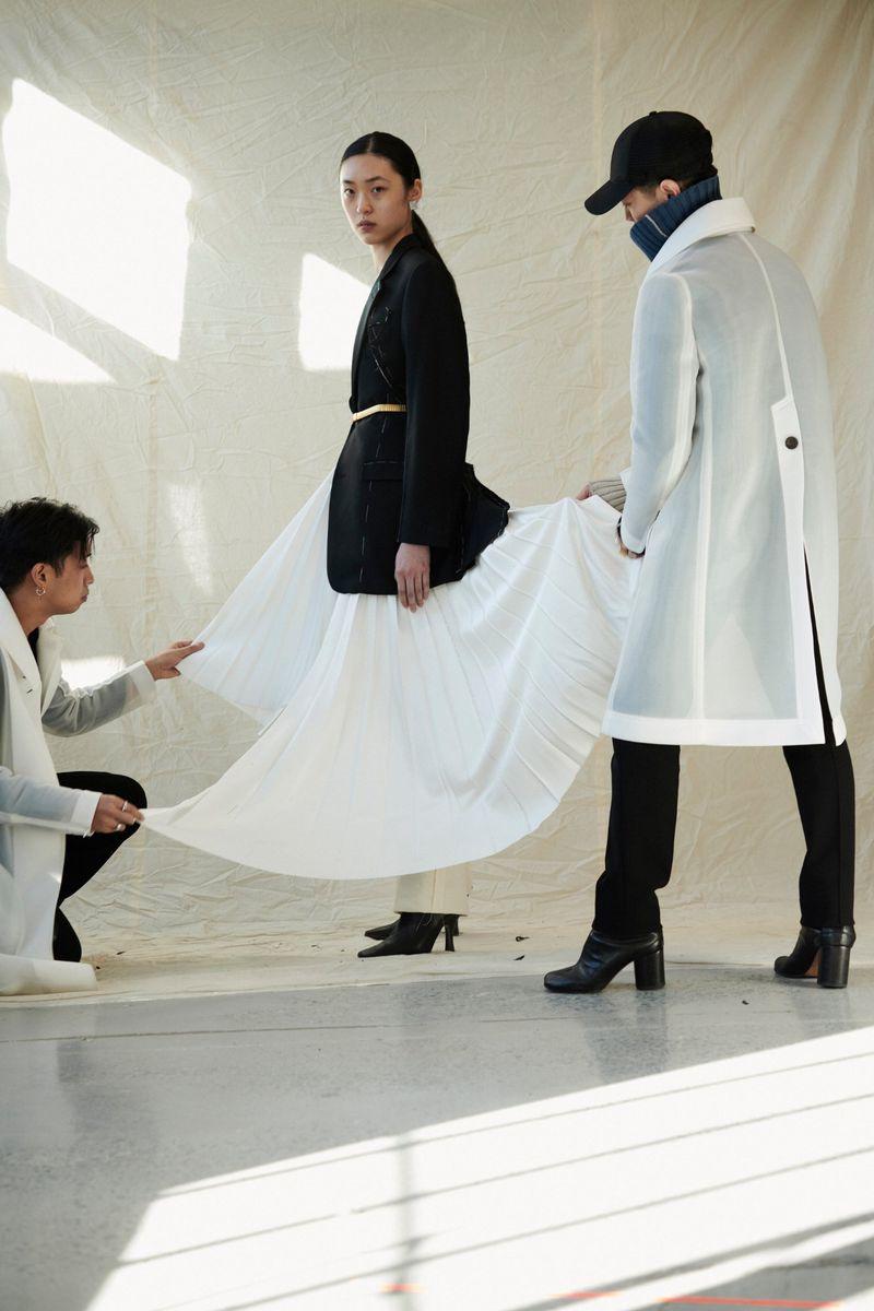 Do (bìa trái) chỉnh áo cho người mẫu bên trong xưởng may của anh tại New York. (Ảnh: Moda Operandi)