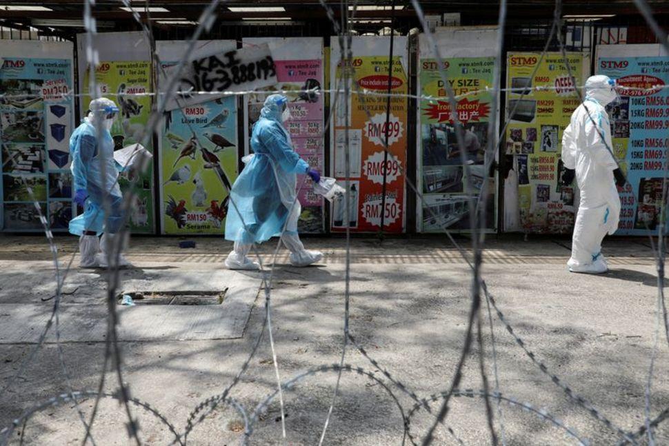 Các nhân viên y tế mặc đồ bảo hộ đi qua hàng rào thép gai trong khu vực màu đỏ được khóa chặt, trong bối cảnh đợt bùng phát virus corona mới, ở Petaling Jaya, Malaysia,