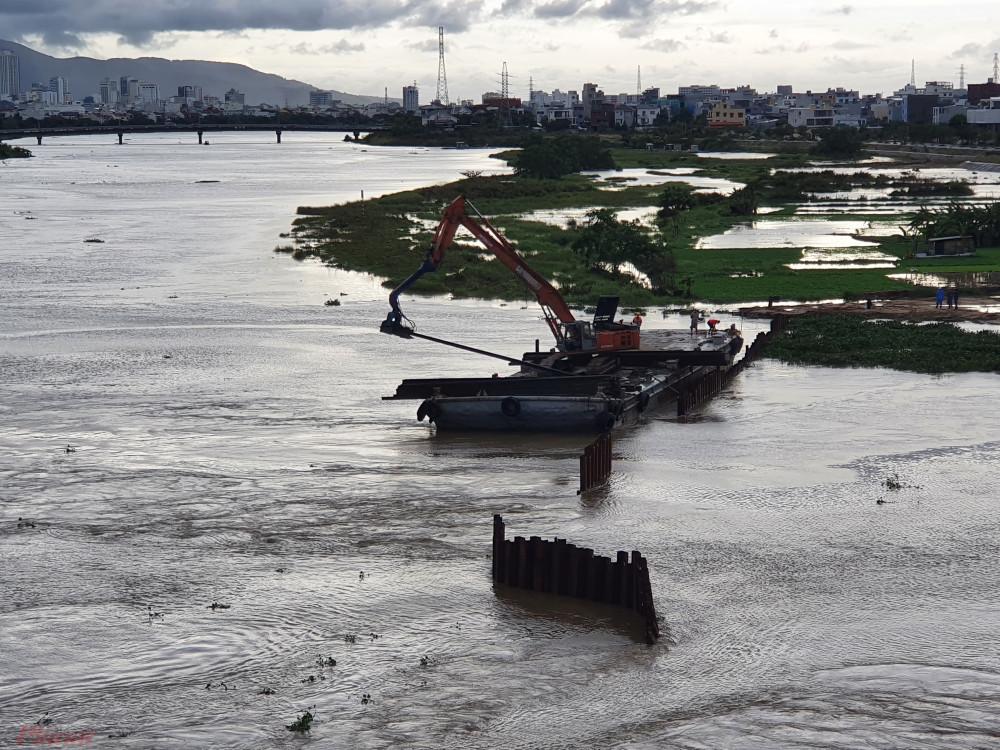 Máy móc được huy động nhổ cừ sắt tại đập tạm ngăn mặn trên sông Cẩm Lệ để khơi thông dòng chảy