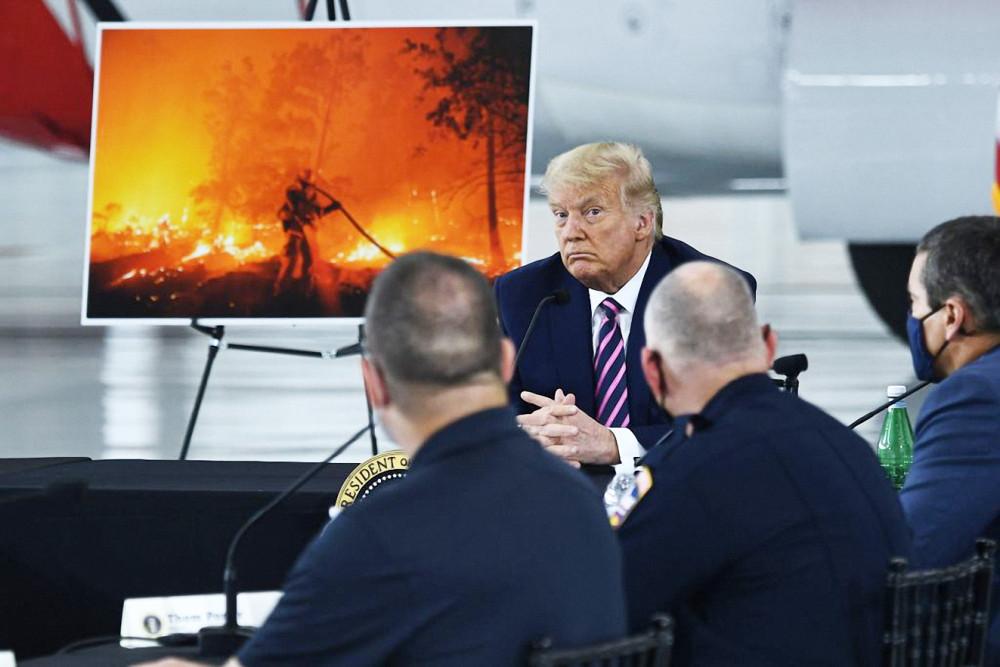 Tổng thống Mỹ Donald Trump lắng nghe Thống đốc bang California Gavin Newsom báo cáo về tình trạng cháy rừng trong cuộc họp tại sân bay Sacramento McClellan vào ngày 14/9 - Ảnh: AFP