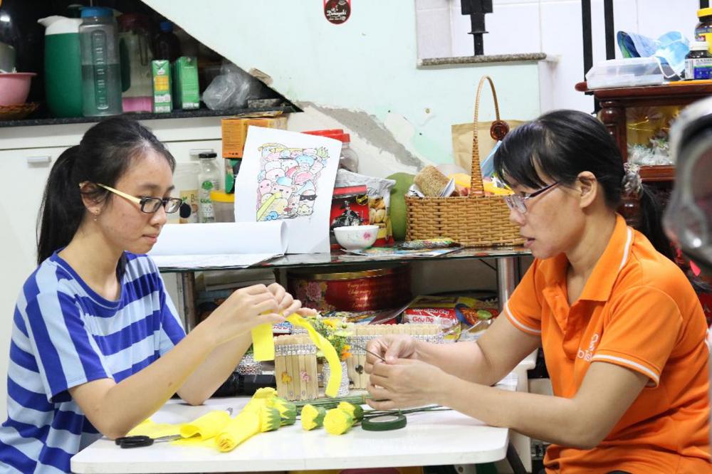 Hà My cùng mẹ làm những hộp đựng bút từ vật dụng tái chế, hoa giấy giúp Hội trong công tác tuyên truyền chống rác thải nhựa tại địa phương