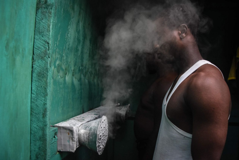 Nhiều người dân ở các nước châu Phi vẫn áp dụng các phương pháp truyền thống mà họ tin là có thể chữa trị được coronavirus. Trong ảnh là một người đàn ông đang xông hơi bằng khói từ lá cây tại nhà một thầy lang trong vùng - Ảnh: Ericky Boniphace/AFP/Getty Images