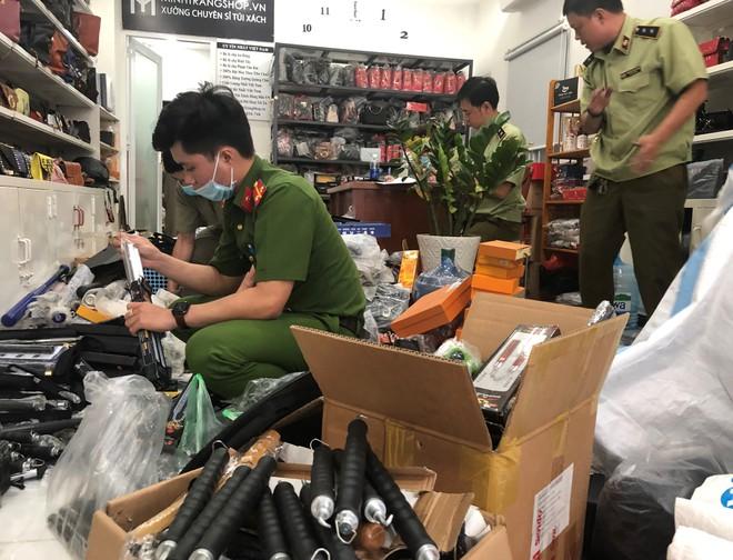 Lực lượng chức năng thu giữ tang vật hung khí tại cửa hàng