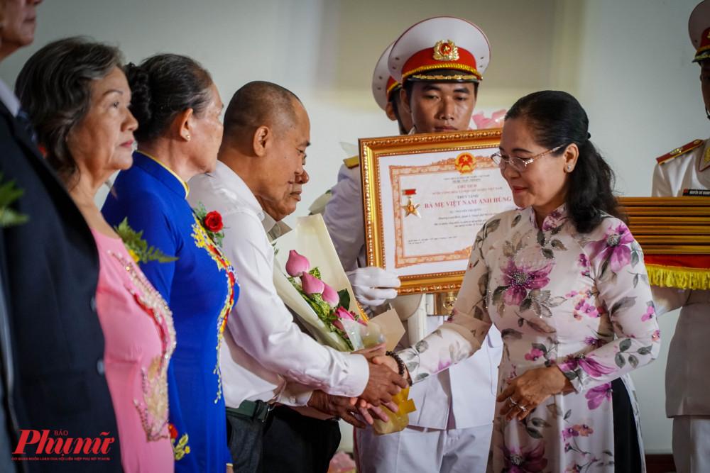 Bà Nguyễn Thị Lệ - Chủ tịch HĐND TPHCM bắt tay chúc mừng đại diện các gia đình được truy tặng dnah hiệu