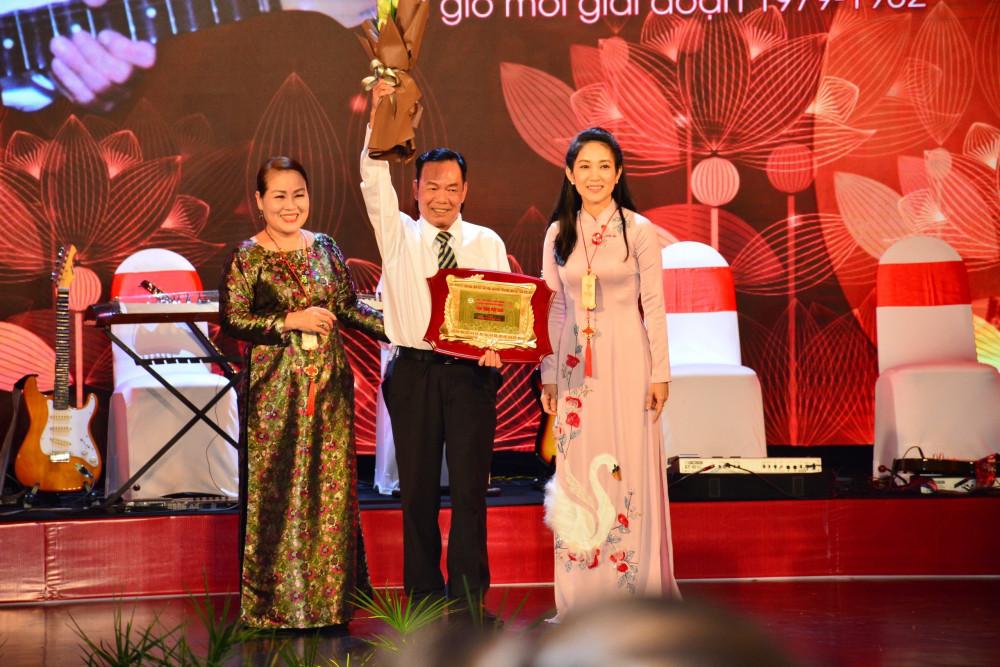 NSND Thanh Hải (giữa) được Phó Giám đốc sở Văn hoá - Thể thao TPHCM bà Nguyễn Thị Thanh Thuý và NS ƯT Huỳnh Liên trao hoa và