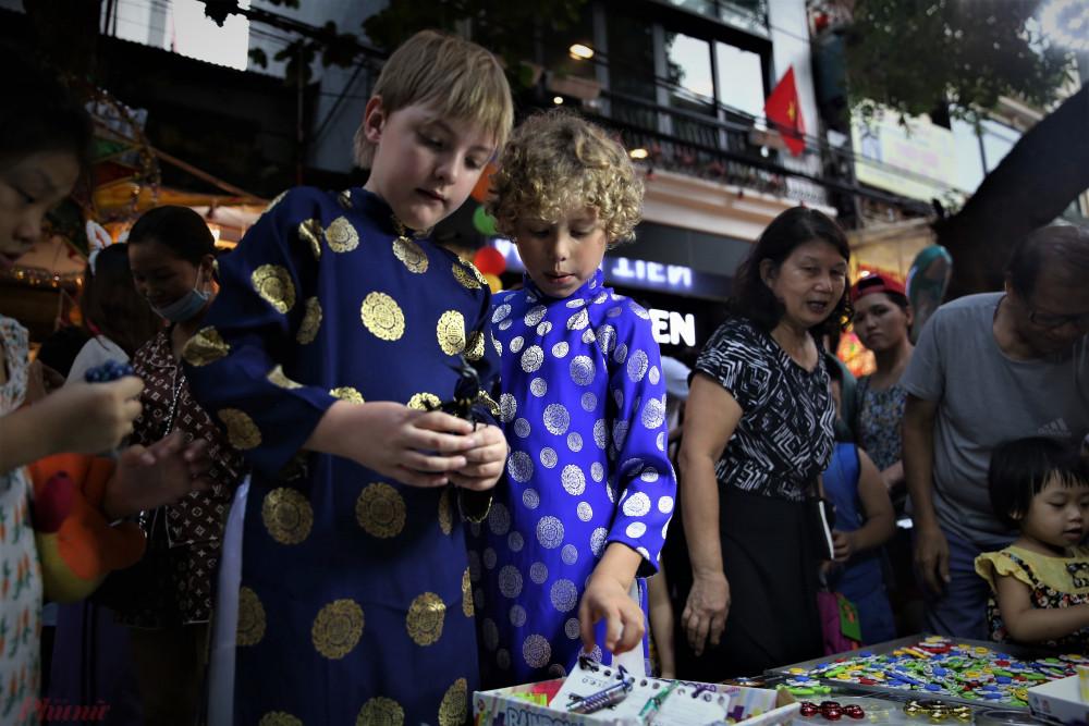 Những đứa trẻ nước ngoài cũng tỏ ra lạ lẫm, thích thú với cảnh nhộn nhịp đầy sắc màu của phố đi bộ Hàng Mã.