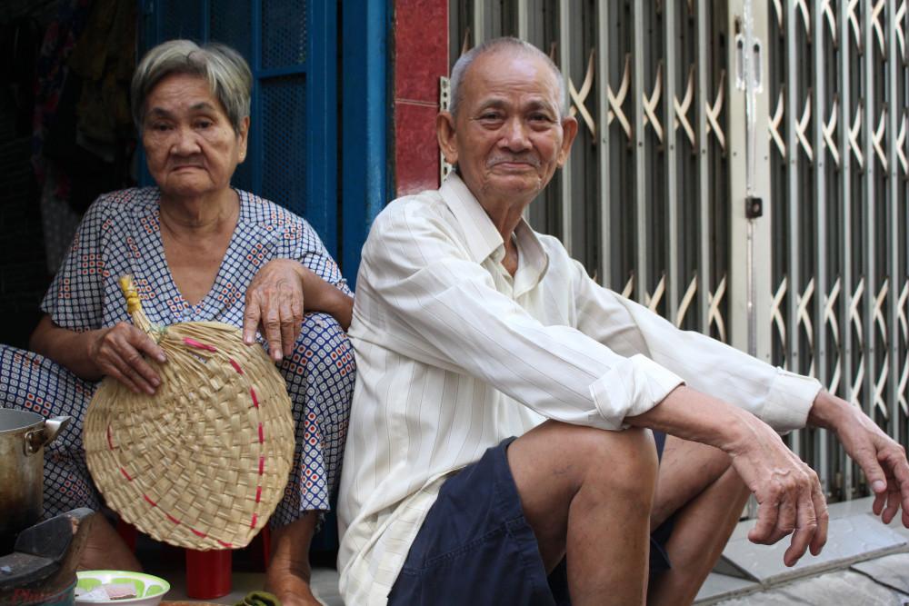 Vợ chồng ông Tôn ngồi trước ngôi nhà siêu nhỏ của gia đình
