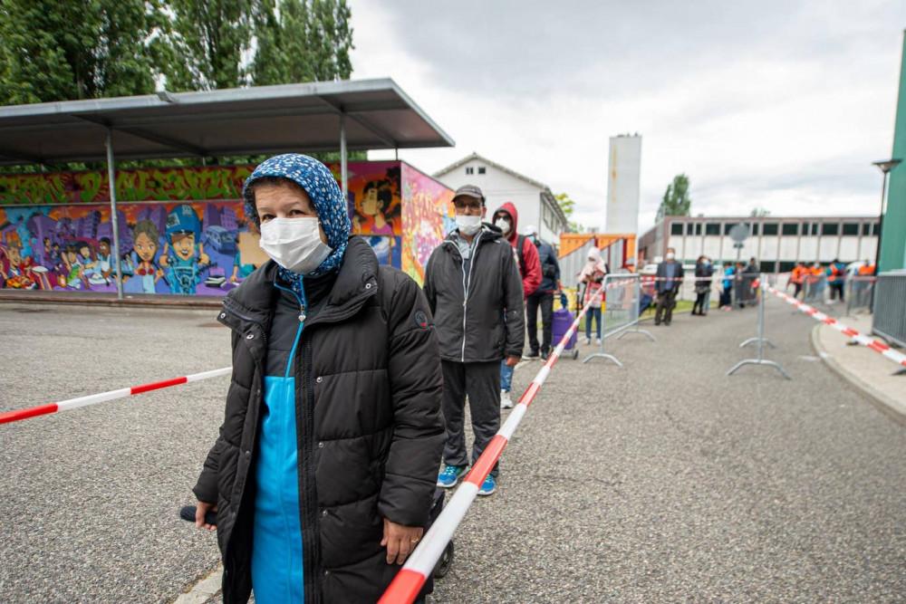 Ở thành phố Geneva, những hàng người dài đang chờ để được nhận khẩu phần ăn trong mùa đại dịch coronavirus - Ảnh: Getty Images