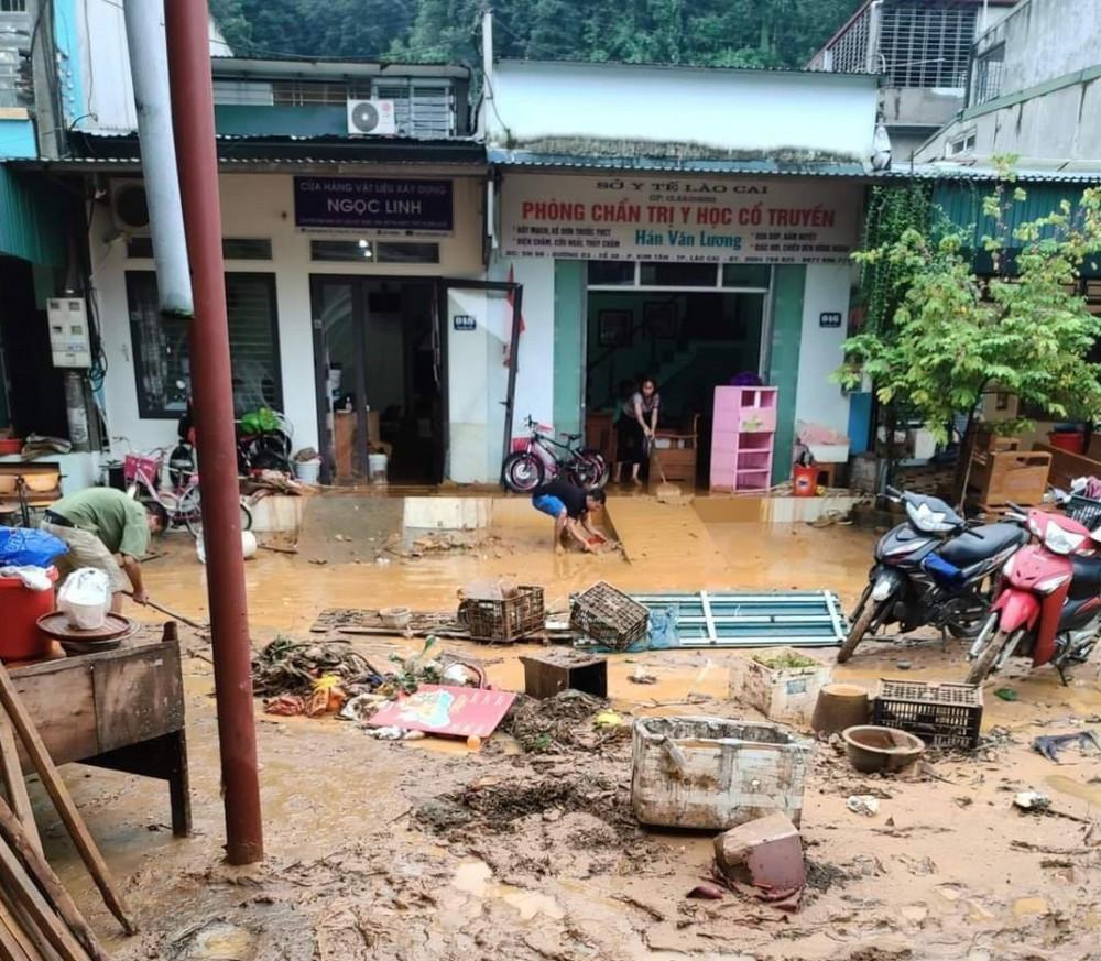 Người dân dọn dẹp bùn rác sau khi nước rút đi.