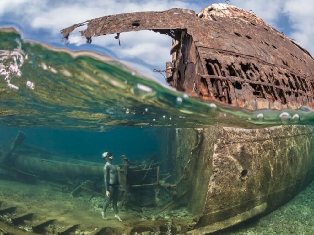 Một người thợ lặn tự do đang đứng quan sát một con tàu bị đắm nhiều năm với phần thân đã mục nát