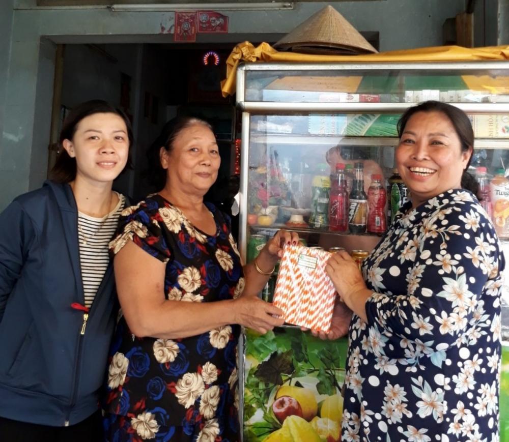 Chị Trần Thị Thanh Loan (bìa phải) tặng ống hút giấy cho tiểu thương kinh doanh ngành hàng ăn uống tại chợ.