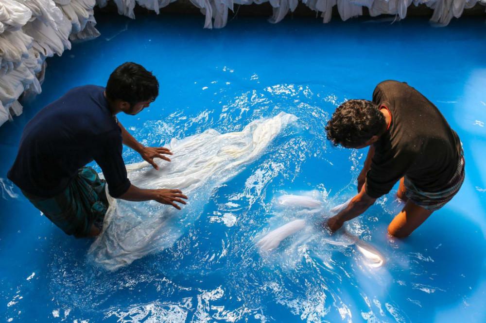 Công nhân đang ngâm tẩm hóa chất cho vải trong một nhà máy ở Bangaldesh - Ảnh: Mohammad Ponir Hossain/NurPhoto/Getty Images