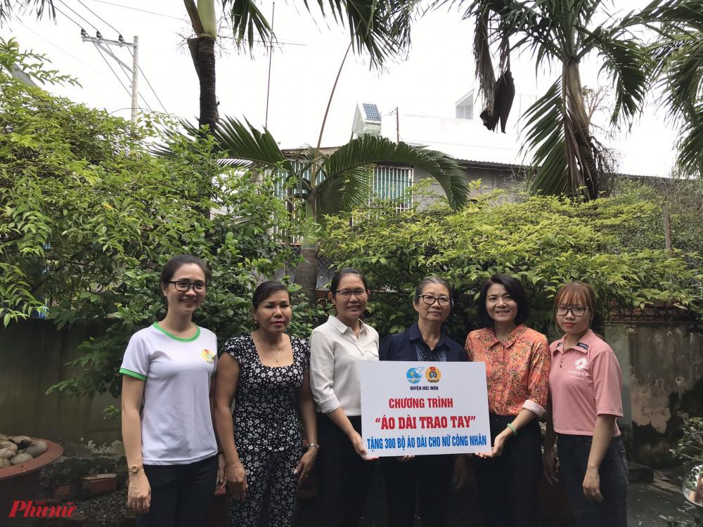 Hội LHPN huyện Hóc Môn trao bảng tượng trưng tặng áo dài cho nữ công nhân các khu nhà trọ trong chương trình 'Áo dài trao tay'.