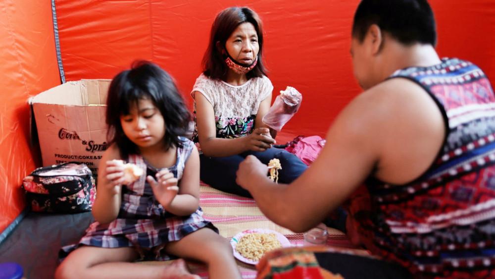 Một gia đình Philippines ăn mì gói trong một căn lều sơ tán tạm bợ giữa đợt bùng phát dịch COVID-19 ở Manila - Ảnh: Reuters