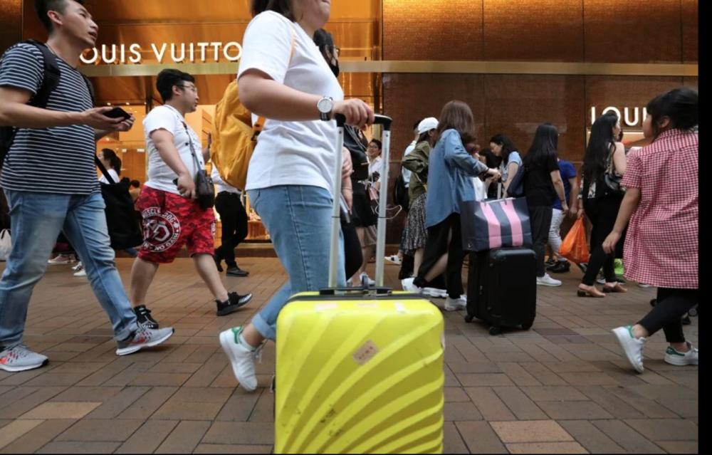 """Mọi người đi ngang qua một cửa hàng Gucci ở Bắc Kinh.  """"Tuần lễ vàng"""" gần đây của đất nước đã chứng kiến sự gia tăng chi tiêu cho du lịch trong nước và đồ xa xỉ.  Ảnh: Reuters"""