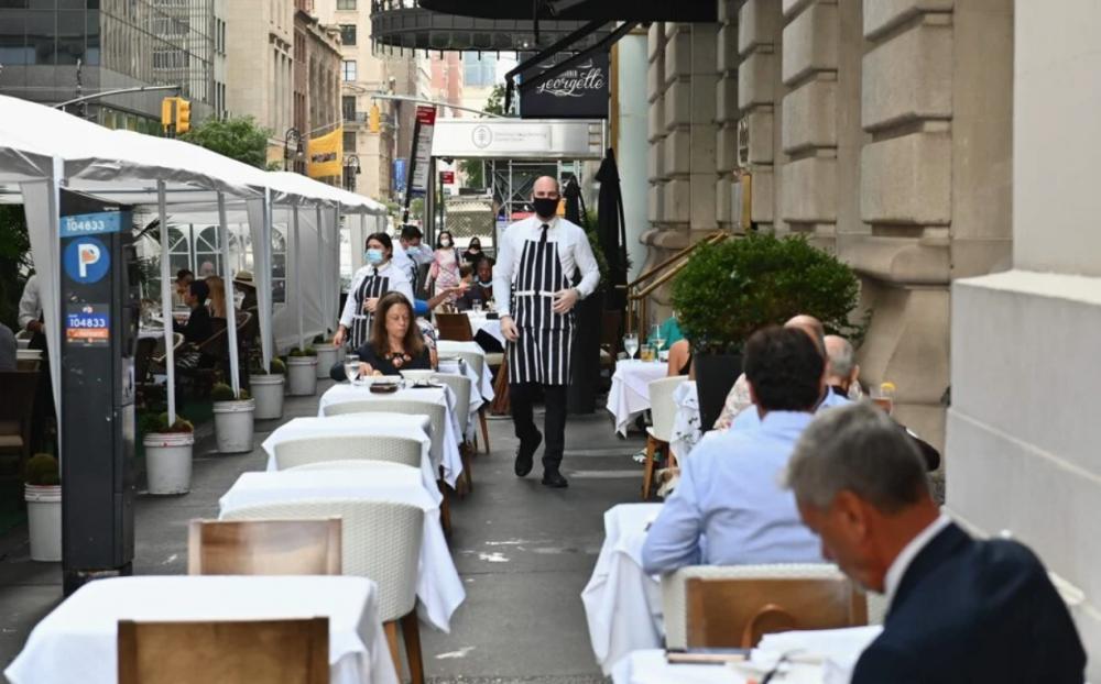 Những người ăn uống ngoài trời gần Đại lộ số 5 ở New York.  Cuộc khảo sát cho biết những người Mỹ giàu có chi tiêu nhiều hơn cho các trải nghiệm, chẳng hạn như ăn uống, du lịch và rượu bia, hơn là hàng hóa xa xỉ.  Ảnh: AFP