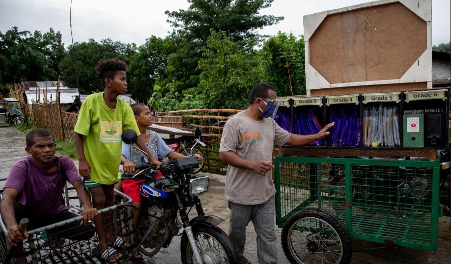 Chiếc xe ba bánh trở thành trường học, với đầy đủ các cấp lớp cần thiết.