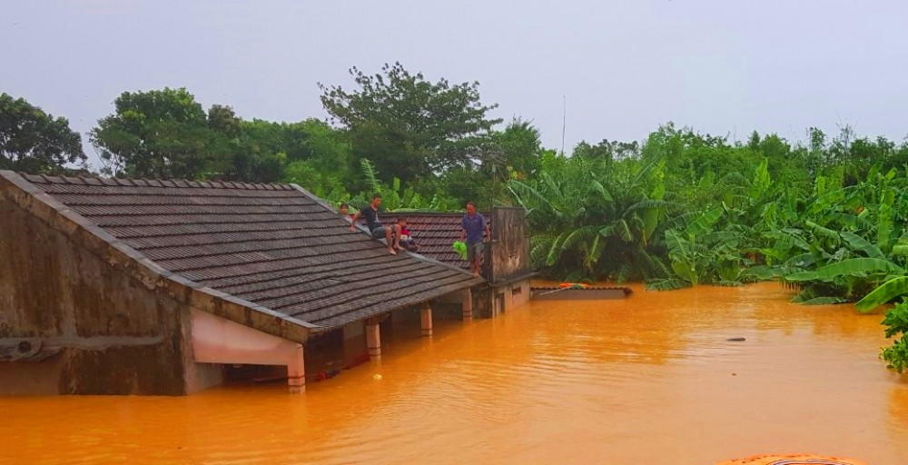 Nước lũ dâng cao, người dân leo trên mái nhà để chờ đội cứu hộ