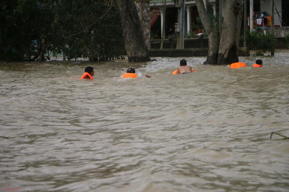 Người dân ở xã Hải Phong bơi đến các điểm phát nước sạch, thức ăn.