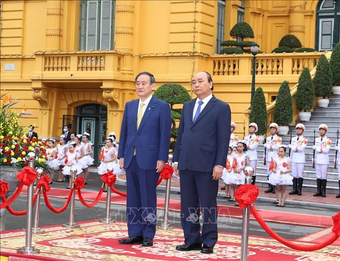 Thủ tướng Nguyễn Xuân Phúc và Thủ tướng Nhật Bản Suga Yoshihide trên bục danh dự, nghe quân nhạc cử Quốc thiều hai nước - Ảnh: Thống Nhất/TTXVN