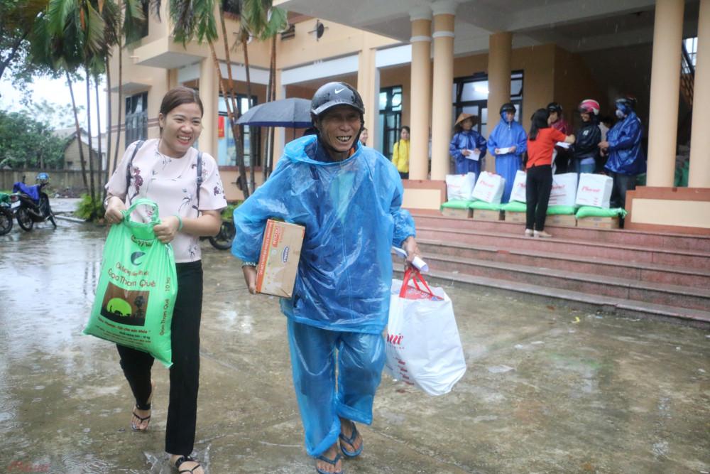 Người dân vùng lũ phấn khởi ra về với những phần quà của Báo Phụ nữ TPHCM.