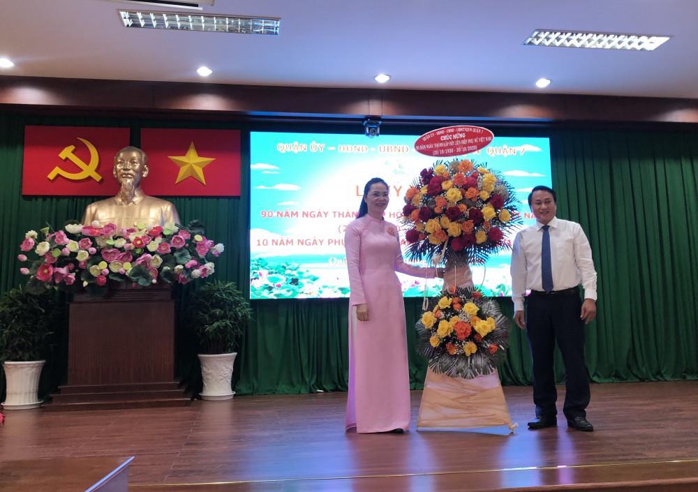Bà Huỳnh Nguyệt Ánh - Chủ tịch Hội liên hiệp Phụ Nữ Quận 7 đón nhận hoa và lời chúc mừng nhân ngày thành lập hội từ lãnh đạo chính quyền. Ảnh: Thanh Huyền.
