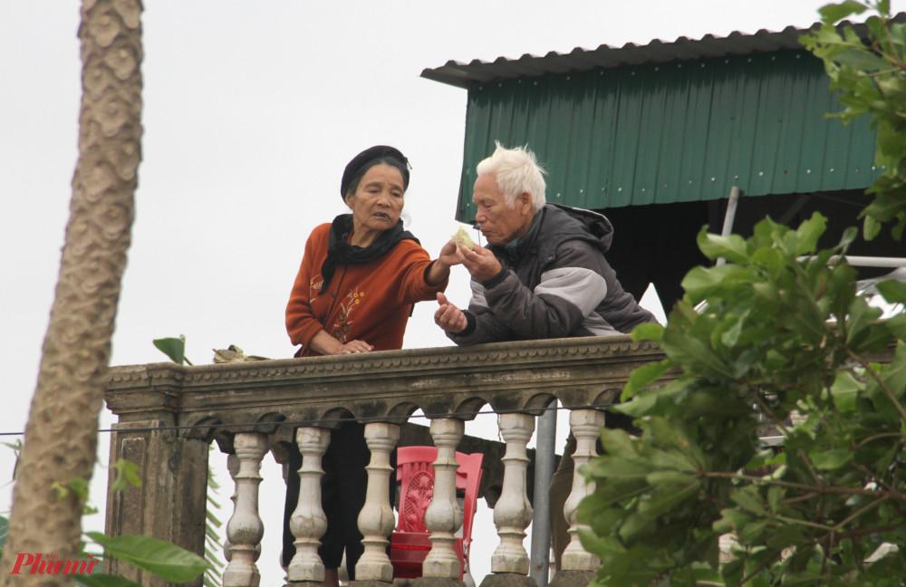 Hai cụ già san sẻ nhau chiếc bánh chưng nhận được từ đoàn cứu trợ