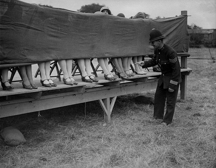 Một cảnh sát đánh giá thí sinh tại cuộc thi hoa hậu mắt cá chân tại Hounslow, London, năm 1930.