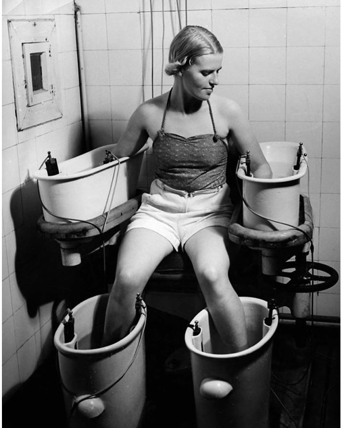 Một người phụ nữ trẻ giữ cánh tay và chân trong bốn bồn tắm với dòng điện chạy qua để cải thiện lưu thông máu, Circa (Mỹ) năm 1938.