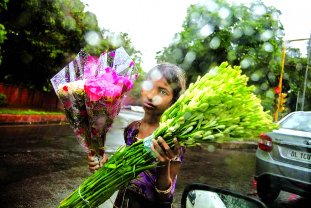Aarti (9 tuổi) đi bán hoa một mình trên con phố Delhi trong mưa bão. Bất chấp rủi ro, hàng triệu trẻ em trên khắp thế giới đang phải làm việc để giúp đỡ gia đình thay vì đi học Ảnh: Stephanie Sinclair