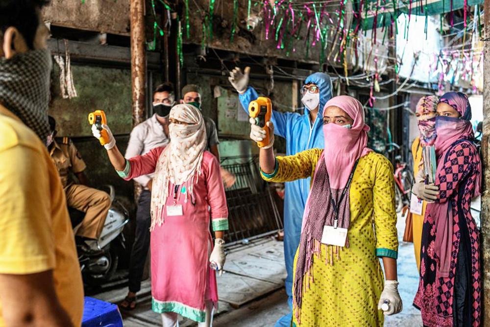 Các nữ nhân viên y tế kiểm tra nhiệt độ của cư dân nhằm phát hiện triệu chứng COVID-19 ở Mumbai, Ấn Độ - Ảnh: Redux