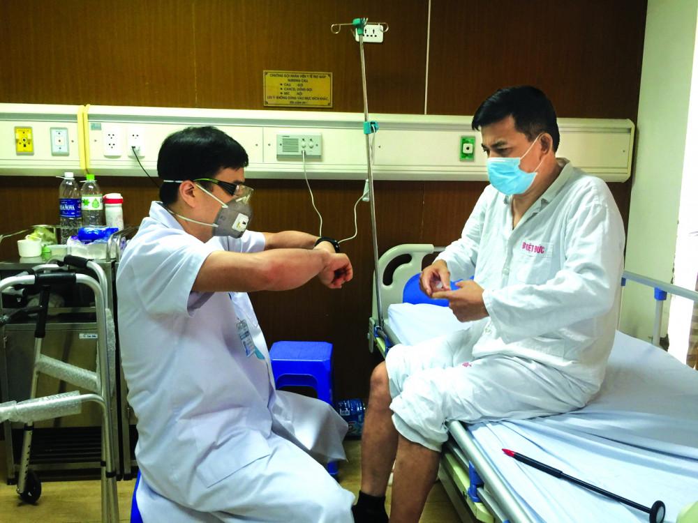 Phó giáo sư - tiến sĩ Nguyễn Lê Bảo Tiến  đang thăm khám cho một bệnh nhân hồi phục tốt sau phẫu thuật đĩa đệm