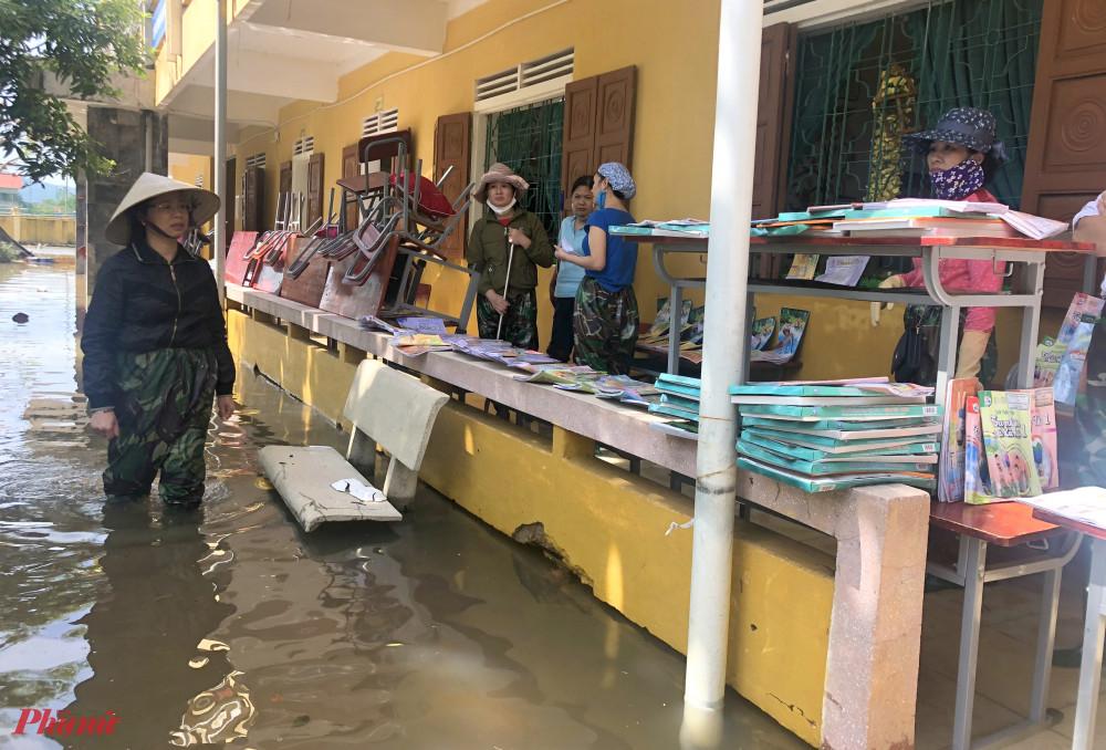 Giáo viên lội nước đi tìm sách vở bị ngập