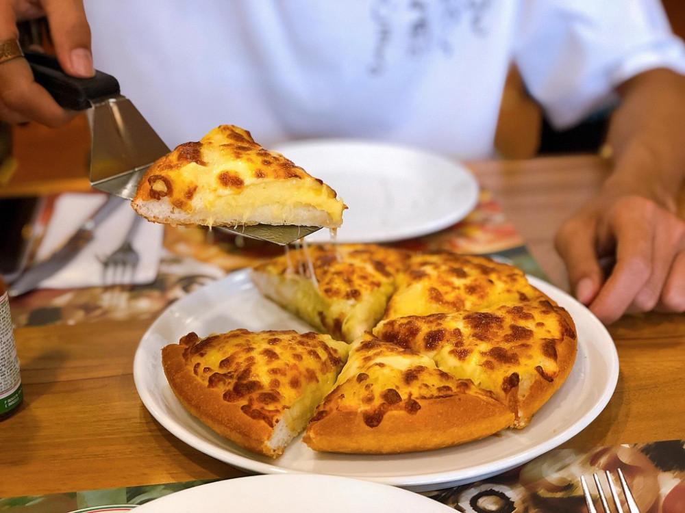 """Pizza sầu riêng: Sầu riêng Monthong thơm phức, béo bùi là lựa chọn số một của các nhà hàng sản xuất loại bánh pizza này. Món bánh kết hợp cùng trái cây có vỏ bánh giòn rụm, vị bơ thơm ngậy và vị sầu riêng ngọt ngào như tan trong miệng. Mặc dù pizza sầu riêng """"được lòng"""" rất nhiều tín đồ sầu riêng nhưng không thể phủ nhận món ăn khá mau ngán do độ béo và ngấy của sầu riêng, bơ và phô mai. Ảnh: Khương Duy,"""