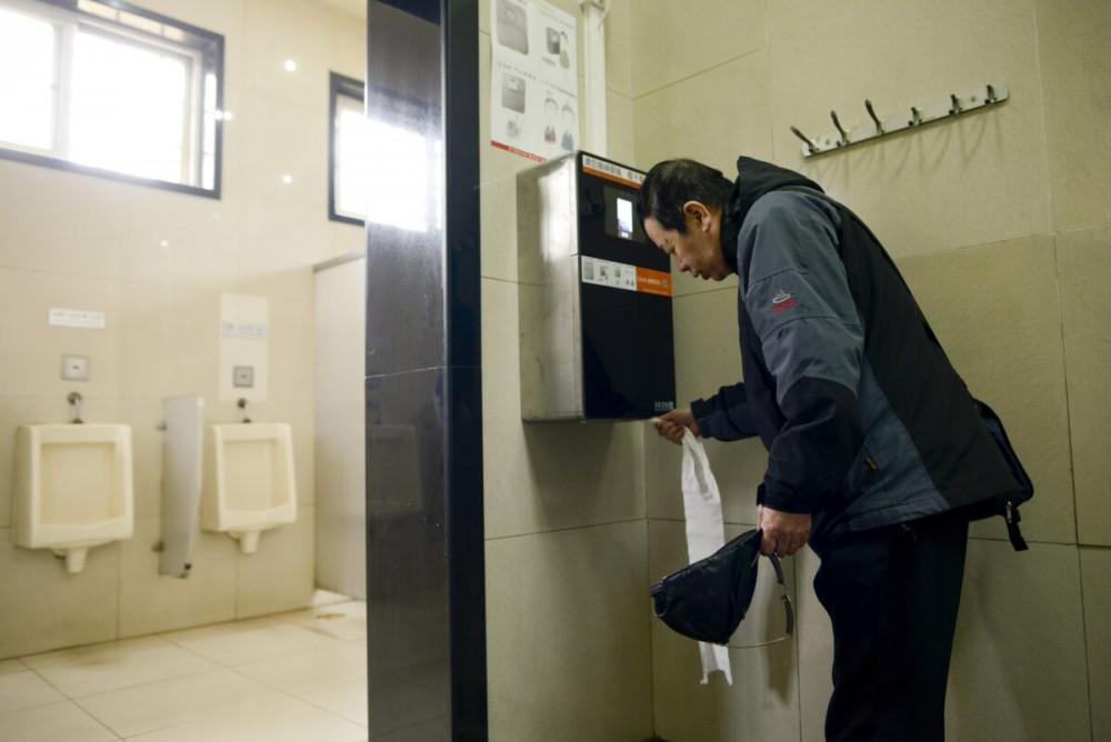 Người dân phải quét trước một camera nhận diện khuôn mặt lắp đặt tring toilet công cộng trước khi có được giấy vệ sinh để sử dụng - Ảnh: Wang Zhao/AFP/Getty Images