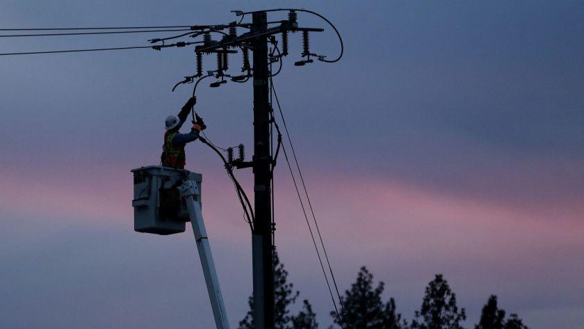 Công nhân điện lực PG&E khôi phục dòng điện sau khi cơn bão quét qua Paradise, California - Ảnh: AP