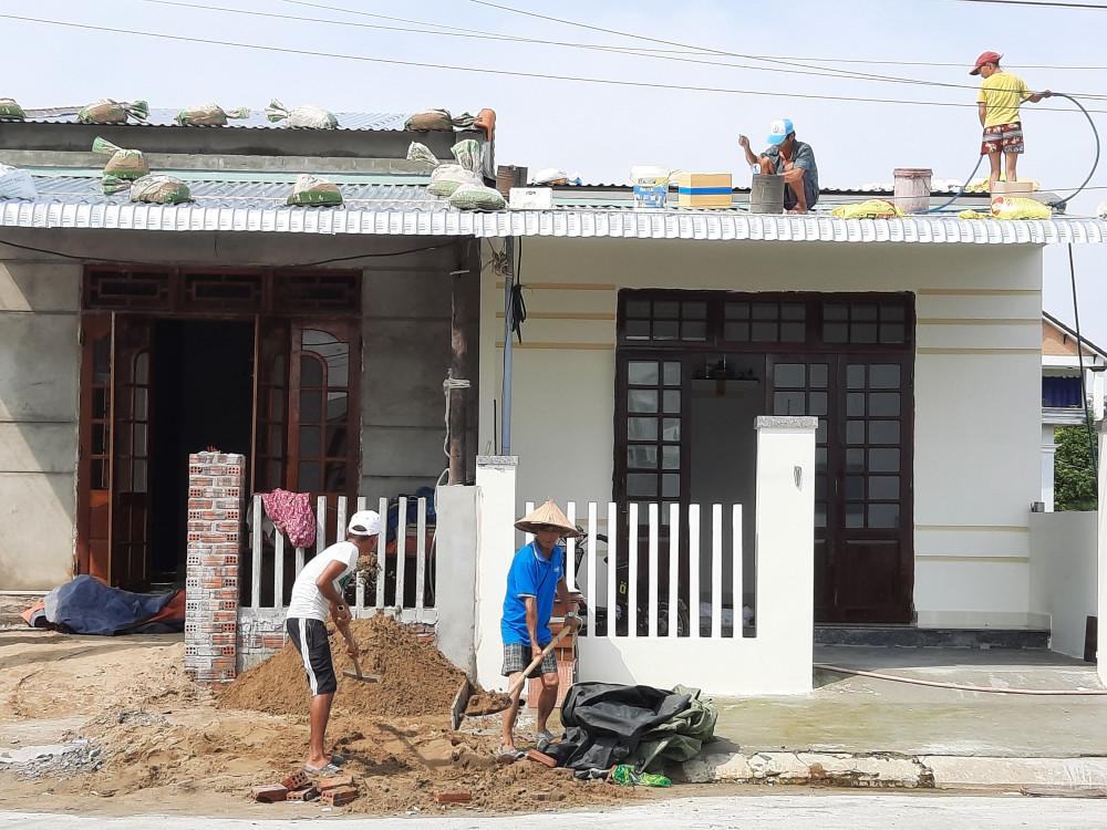 Người dân Quảng Nam đang đưa những bao cát lên mái tôn đề chèn, chống bão