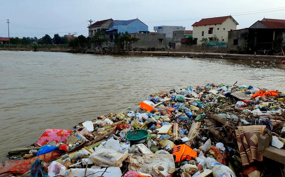 Gần đó, chân cầu An Lạc bắt qua sông Kiến Giang đang tụ lại những bãi rác lớn là vật dụng, tài sản của người dân bị lũ cuốn đi.