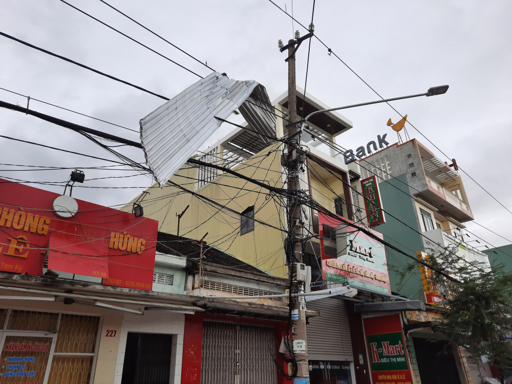 Nhiều tấm tôn bị gió thổi, mắc vào các cây cột điện ở ven đường