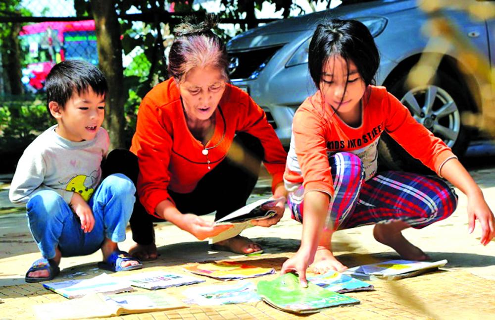 Năm nào ở miền Trung cũng có những đứa trẻ đứng trước sân nhà giũ sách, hong khô - Ảnh: Sỹ hòa
